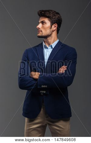 Serious handsome man with arms folded standing isolated on a gray background