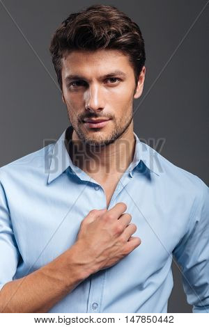 Portrait of a casual handsome man buttoning his shirt isolated on a gray background