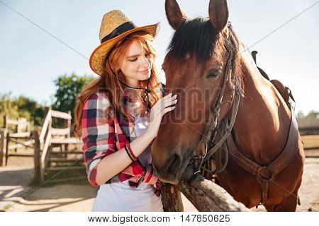 Portrait of smiling tender young woman cowgirl with her horse on ranch