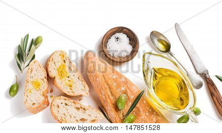 Top view of slices of baguette salt olives fruit with green leaves and bowl of olive oil isolated on white background.