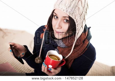 Woman using tablet at cozy home atmosphere on the bed. Young woman with cup tea or coffee in hands enjoying free time with comfort. Soft light and comfy lifestyle concept. Technology in life