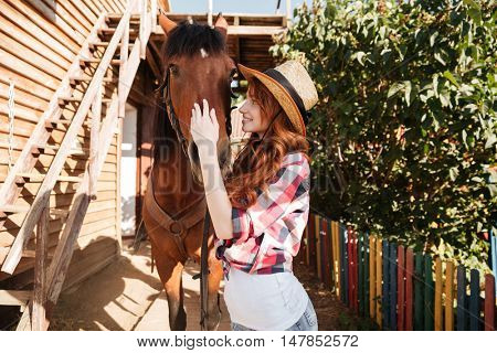 Smiling pretty young woman cowgirl standing and taking care of her horse on farm