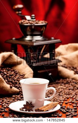 Cup of warm coffee with coffee grinder and burlap sack with roasted beans. Old coffee mill with white mug and spice - cinnamon and anise.