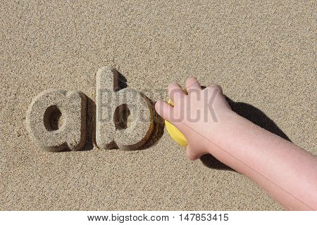 A child playing on beach. The child has made the letters 'abc' in a row. Learning is fun.