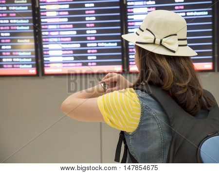 Woman backpacker see her watch at the flight board in the airport for check her flight time.