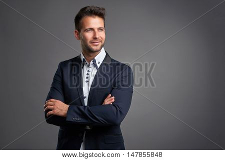 A confident elegant handsome young man standing in front of a grey background in a studio