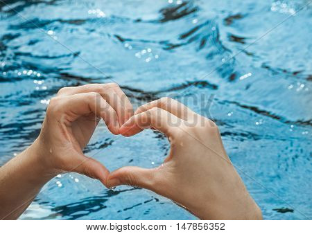 Heart from hands on swimming pool, With place your text (Concept ,Love, Health)