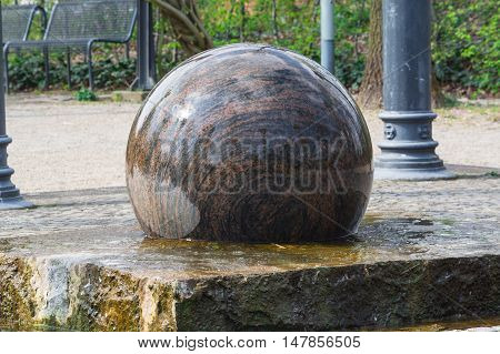 Large floating ball dark granite with decorative elements as Fountain
