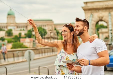 A beautiful young woman is pointing away while her boyfriend is holding a map with the castle of Buda and the Chain Bridge behind them in Budapest, Hungary.