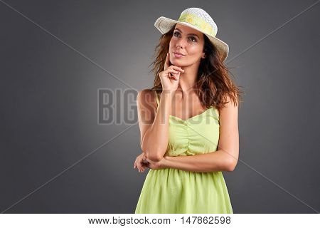 A beautiful young woman thinking in a green dress and a hat