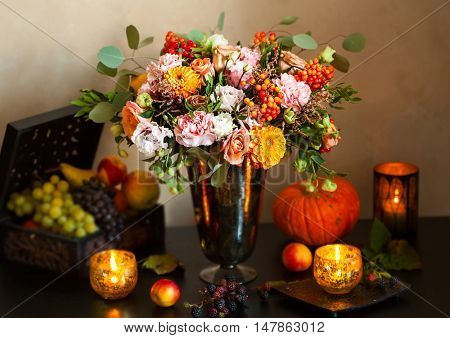 Autumn still life with flowers, pumpkin, fruits and candles