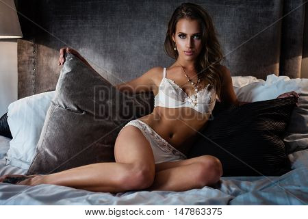 Beautiful lady in sexy lingerie sits in bed