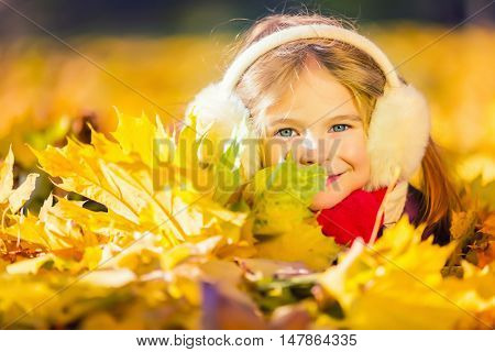 Little girl in earflaps playing with autumn leaves in the park