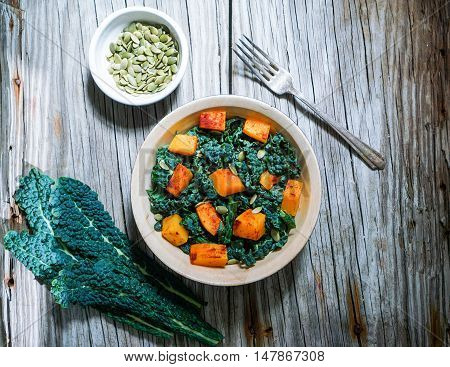 Kale Salad with Butternut Squash and Pumpkin Seeds on Rustic Background