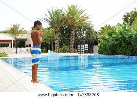 Boy preparing to jump into swimming pool.