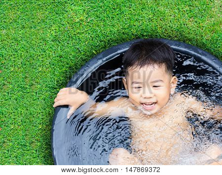 cute baby boy taking water procedures in summer garden