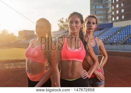 Group of fit young sportswomen standing on athletics stadium and posing