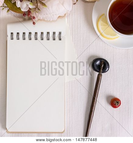 Mockup photography with flowers notebook and pen with nib. Desktop workplace designer artist painter top view. Modern trend template for advertising.