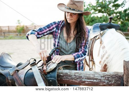 Pretty young woman cowgirl in hat working and preparing saddle for riding horse