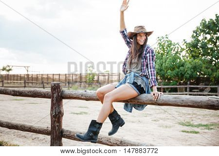 Cheerful attractive young woman cowgirl sitting on fence and having fun