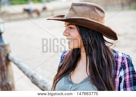 Closeup of smiling pretty young woman cowgirl in hat