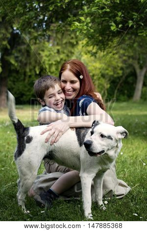Nice white boy with beautiful young woman on spring sunny garden. Portrait of boy with mother and their dog. Happy family in sunny day. Mother and sun spend leisure time activitie. Playing with dog.