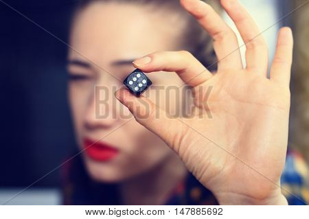 Hand girl holding a dice for a game of backgammon.