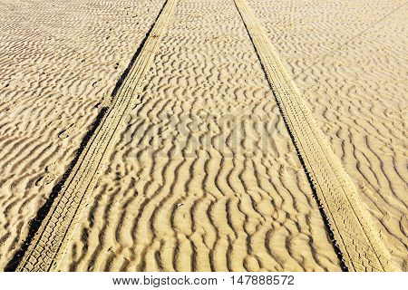 Straight parallel wheel tracks in the the sand dunes.
