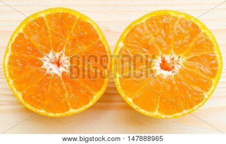 Organic orange fruit. Slices on soft wooden background