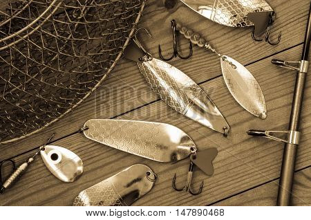 Fishing accessories for summer. Tackle bait lure jig hook net. Wooden background. Outdoor activity and leisure concept. Toned.