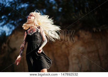 Young Tattoo Blonde Girl On Black Dress And Glasses Posed Background Of Career