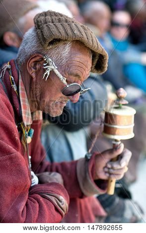 LAMAYURU, INDIA - JUNE 17, 2012: Man with prayer wheel praying in Lamayuru Gompa during Yuru Kabgyat festival.