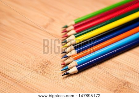 Colored pencils focus isolated to first pencil tip on wood background