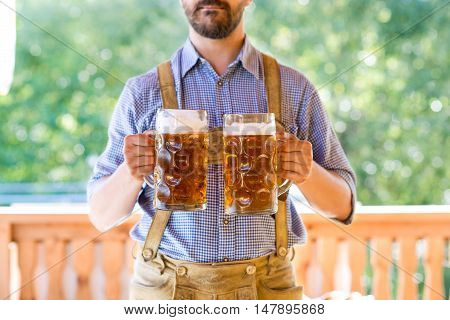 Unrecognizable young men in traditional bavarian clothes holding two mugs of beer. Oktoberfest. Sunny summer garden.