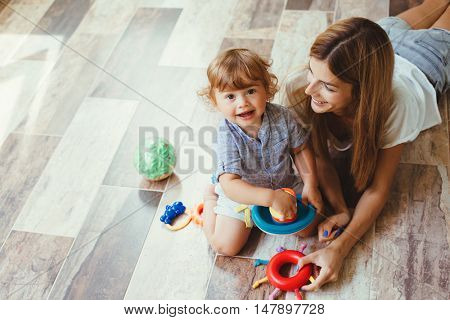 Mom playing with her son with toys on the warm clean floor at home