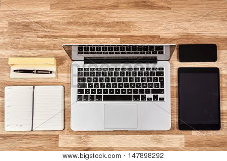Notebook, Laptop, Tablet And Mobil Phone On Oak Table
