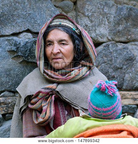 TURTUK, INDIA - JUNE 13: Balti woman carrying baby on the street.