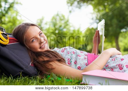 Portrait of a Young Woman Using a Tablet in a Park