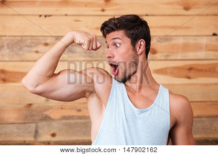Funny amazed young man looking at his biceps over wooden background