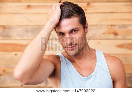 Closeup of confident attrative young man over wooden background