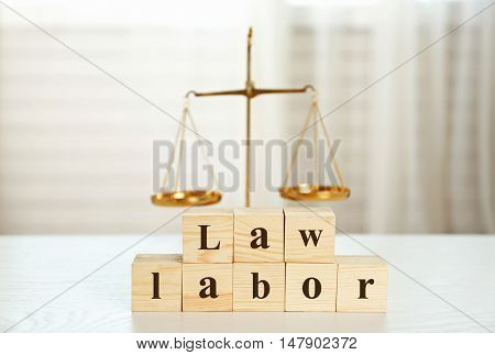 Wooden cubes with phrase LAW LABOR and scales on a table