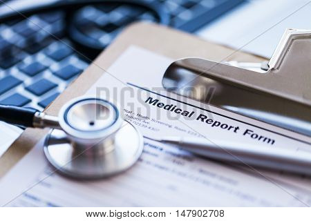 Stethoscope and Medical Report on a Laptop