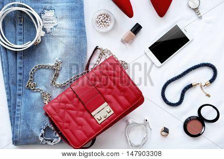 Stylish women clothing set on bed background