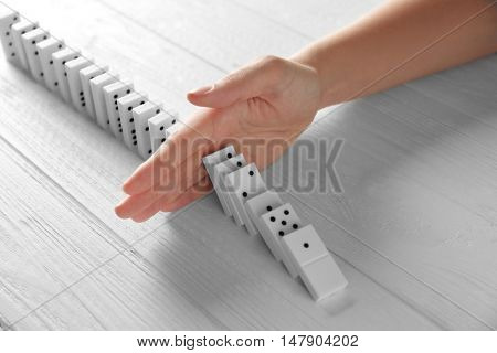 Female hand stopping domino effect on wooden table