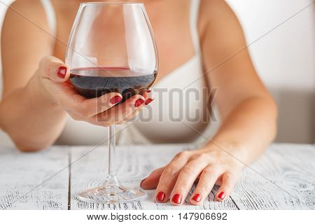 Woman in bra drinking red wine in home