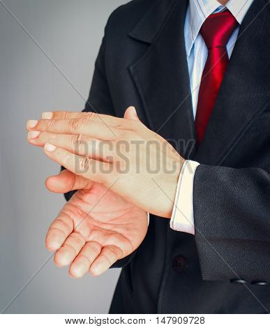 Businessman in suit with red tie showing gesture applaud on gray background.