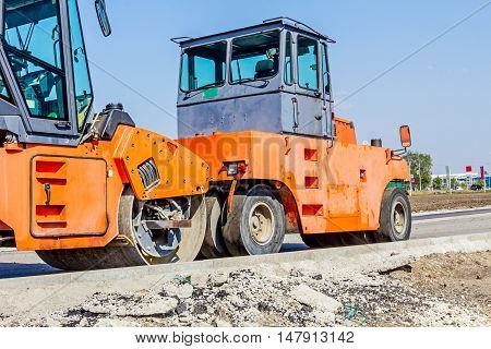 Group of machines for spreading asphalt are parked after road construction at building site.