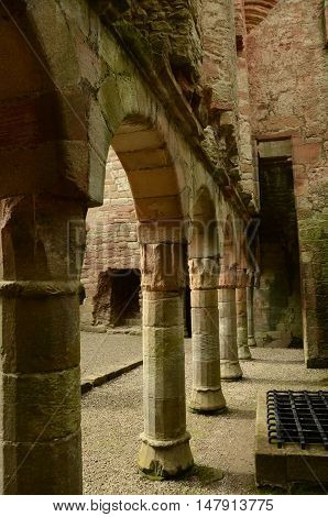 A view of the supporting columns and arches beneath the façade wall in Crichton castle