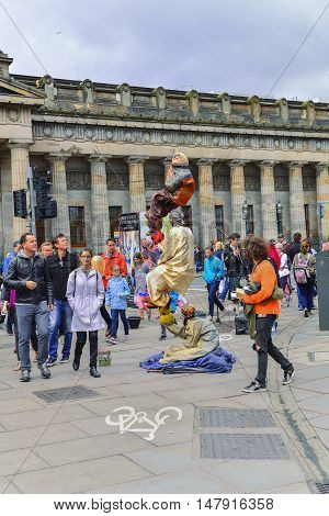 AUGUST 13, 2016--EDINBURGH, SCOTLAND--Tourists and locals enjoy street performers during the Fringe in Edinburgh, Scotland. The Fringe is the world's largest arts festival