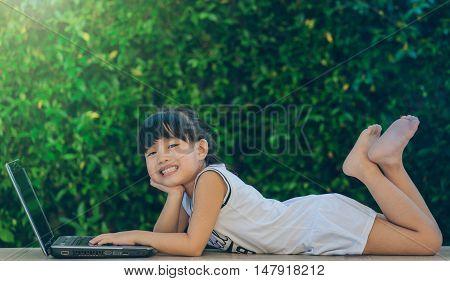 Happy little girl having fun play laptop